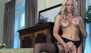 A blonde with nylons on is alone on the seat, massaging herself